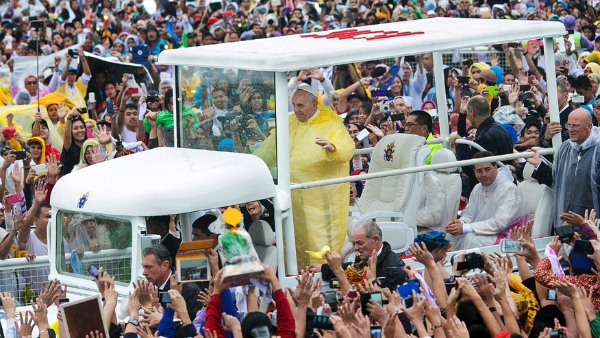 Pope Francis waves to the crowd as he arrives at Quirino Grandstand to celebrate his final Papal Mass in Manila, Philippines, Sunday, Jan. 18, 2015. Millions filled Manila's main park and surrounding areas for Pope Francis' final Mass in the Philippines on Sunday, braving a steady rain to hear the pontiff's message of hope and consolation for the Southeast Asian country's most downtrodden and destitute. (AP Photo/Ron Soliman)