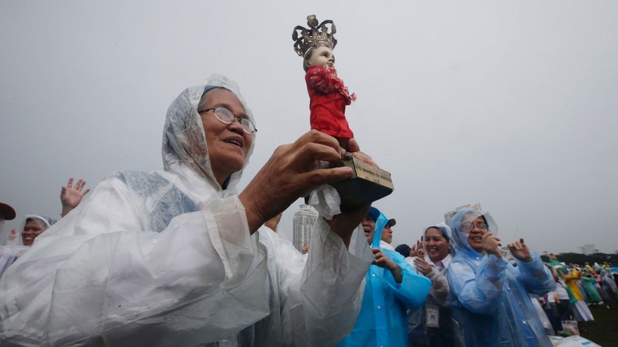 A nun holds the statue of the infant Jesus in the rain as Pope Francis celebrates his final Mass in Manila, Philippines, Sunday, Jan. 18, 2015. Millions filled Manila's main park and surrounding areas for Pope Francis' final Mass in the Philippines on Sunday, braving a steady rain to hear the pontiff's message of hope and consolation for the Southeast Asian country's most downtrodden and destitute. (AP Photo/Bullit Marquez)