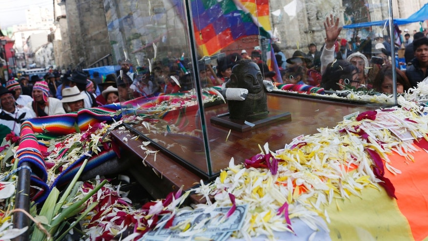 "Crowds accompany the Bolivian deity statuette ""illa of Ekeko"" as it is driven to the Alasitas Fair, in which Ekeko is the central figure, in La Paz, Bolivia, Saturday, Jan. 24, 2015. The pre-Columbian figurine that symbolizes abundance was recently returned to Bolivia by the National Museum of Berna in Switzerland, 156 years after being taken away from its native country. ""Alasitas"" is an Aymaran word that means ""buy me,"" and is the name of the annual fair where people buy miniature items that represent things they hope to attain within the year.  (AP Photo/Juan Karita)"