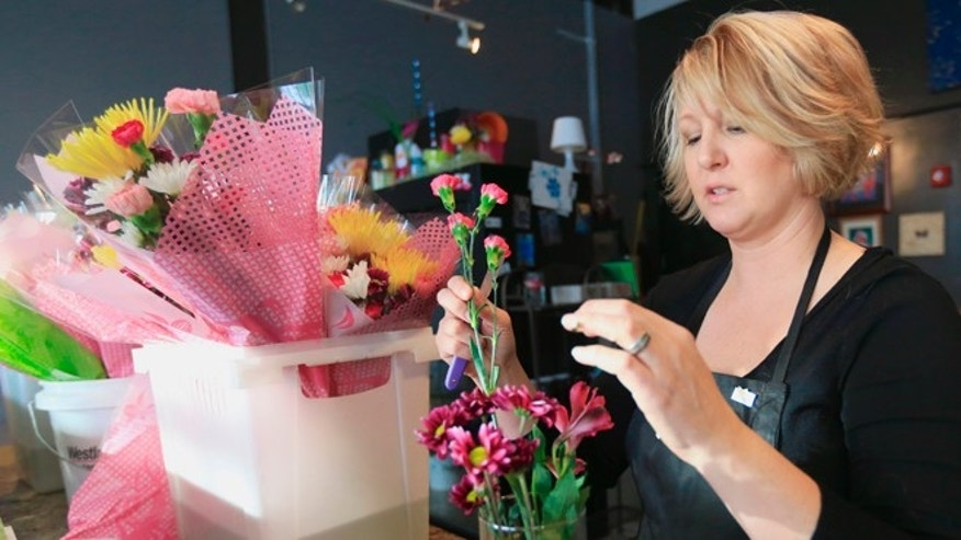 Rhonda Bullington, owner of Loess Hills Floral Studio in Council Bluffs, Iowa, makes a flower arrangement in Council Bluffs, Iowa, Friday, Feb. 6, 2015. The vast majority of cut flowers used in florists' bouquets are imported and Bullington says she hasn't had any customers asking for locally-grown flowers.  (AP Photo/Nati Harnik)