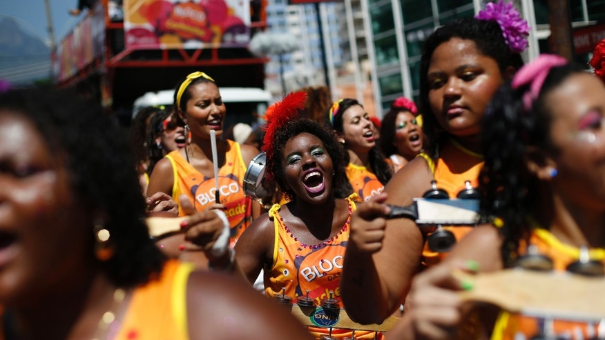 Women play samba music during a street party promoting black pride and  encouraging Afro-Brazilian women to flaunt their curls in Rio de Janeiro, Brazil, Sunday, Feb. 8, 2015. Sunday's curl-power celebration in Rio de Janeiro is one of hundreds of street parties that are kicking off in the run-up to Carnival, which starts on Friday. (AP Photo/Silvia Izquierdo)