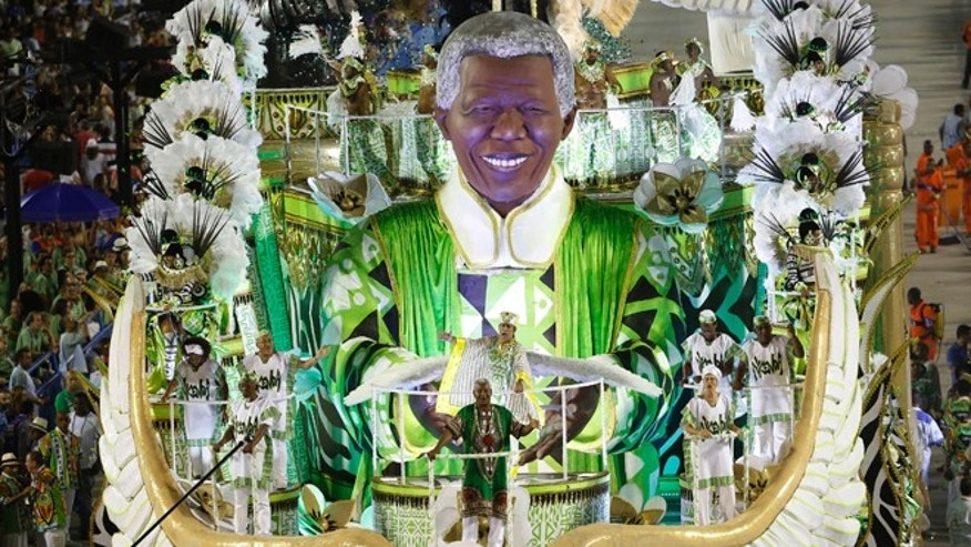 Performers from the Imperatriz Leopoldinense samba school parade in a float with the sculpture depicting Nelson Mandela, during carnival celebrations at the Sambadrome in Rio de Janeiro, Brazil, Tuesday, Feb. 17, 2015. (AP Photo/Leo Correa)
