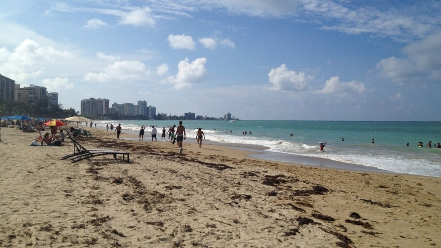 In this Oct. 2014 photo, beachgoers enjoy the sun and sand at Isla Verde Beach in San Juan, Puerto Rico. Puerto Rico, a U.S. territory, offers all the comforts of domestic travel - easy entry, no extra charges for cell phone service, and the U.S. dollar as the currency - along with Caribbean beaches and Latin culture, waterfalls, colonial Spanish history and good food and drink. (AP Photo/Kristi Eaton)