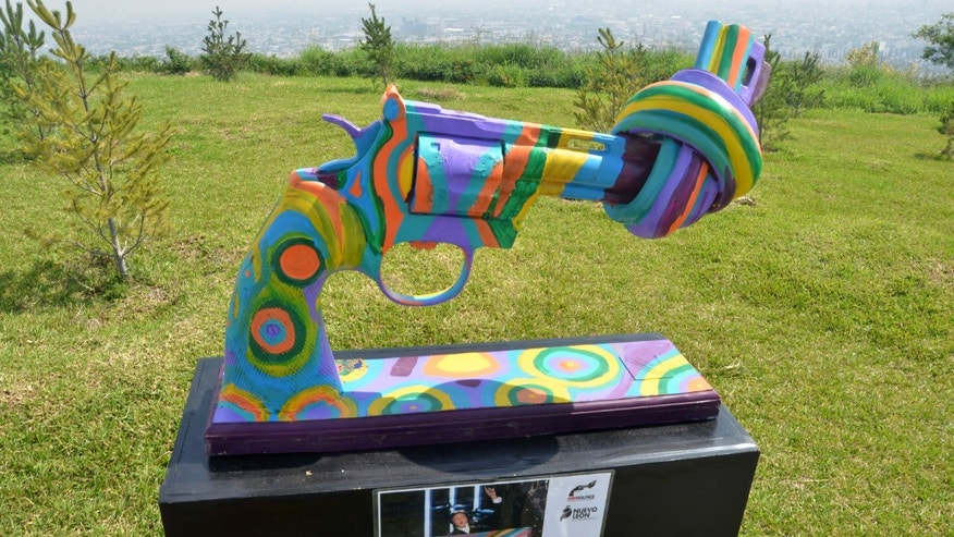 In this Thursday April 2, 2015 photo, a knotted gun sculpture painted by British musician and ex-Beatle Sir Paul McCartney is displayed at a park in the city of Monterrey, Mexico. Thirteen knotted gun sculptures painted by various artists are on display in this city that for years has been plagued with violence generated by warring drug cartels. The original knotted gun sculpture was designed and created by Carl Fredrik Reutersward as a memorial to John Lennon after he was shot and killed in 1980 and is now displayed outside of the United Nations headquarters in New York City. (AP Photo/Emilio Vazquez)