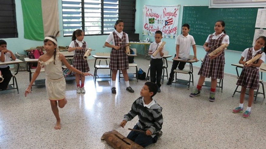 In this April 10, 2015 photo, Brayan Lopez, 9, plays a Taino wood drum while students perform a ceremonial dance in San Lorenzo, Puerto Rico. Brayan is a fourth grader and one of the designated caciques - or chieftains - because of his musical skills. He gets to blow a conch shell while other students gather around him and beat on the small, elongated wooden drums. (AP Photo/Danica Coto)