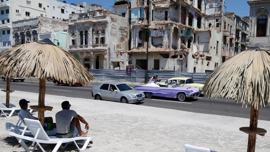 People sit on deck chairs on an artificial beach as a bride and groom ride a classic American convertible car on the Malecon in Havana, Cuba, Thursday, May 21, 2015. The artificial beach is part of a collective artistic intervention named ¨Behind The Wall¨for the Havana Biennial Art Fair which starts on May 22. (AP Photo/Desmond Boylan)