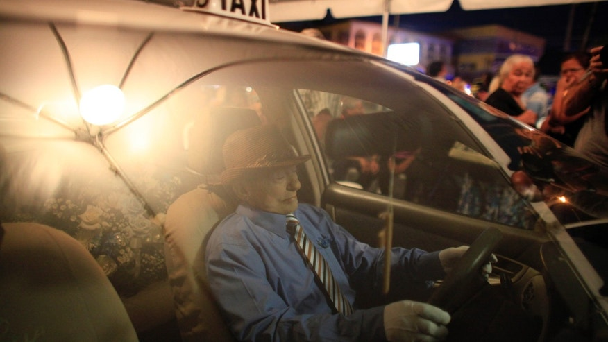 The body of Victor Perez is propped up inside his taxi during his wake in Aguas Buenas, Puerto Rico, Sunday, May 24, 2015. Perez Cardona, 73, a cancer patient and a veteran taxi driver known in the town of Aguas Buenas as 'Vitín the driver', joined the curious tradition of unusual wakes to honor his profession being veiled as if he were driving his taxi. (AP Photo/Ricardo Arduengo)