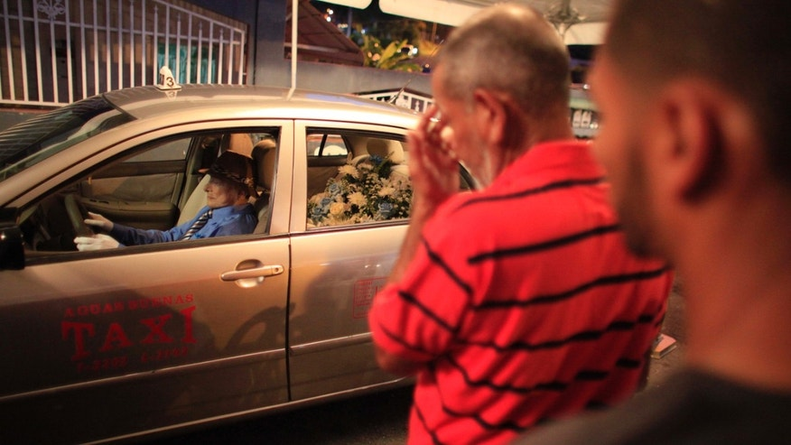 People attend the wake of taxi driver Victor Perez Cardona, whose body is propped up inside his taxi in Aguas Buenas, Puerto Rico, Sunday, May 24, 2015. Perez Cardona, 73, a cancer patient and a veteran taxi driver known in the town of Aguas Buenas as 'Vitín the driver', joined the unusual tradition of wakes  to honor his profession being veiled as if he were driving his taxi. (AP Photo/Ricardo Arduengo)
