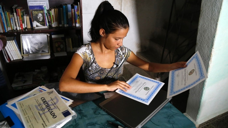 In this May 22, 2015 photo, Eleyn Ponjuan, who is taking a course in independent journalism led by U.S. professors via video link inside the U.S. Interests Section, arranges certificates for her completed English and journalism courses, at home in Havana, Cuba.  âThese courses are a very good opportunity for us, for those who donât have any resources, who donât have work, and I donât think there is anything wrong with that,â said Ponjuan. (AP Photo/Desmond Boylan)