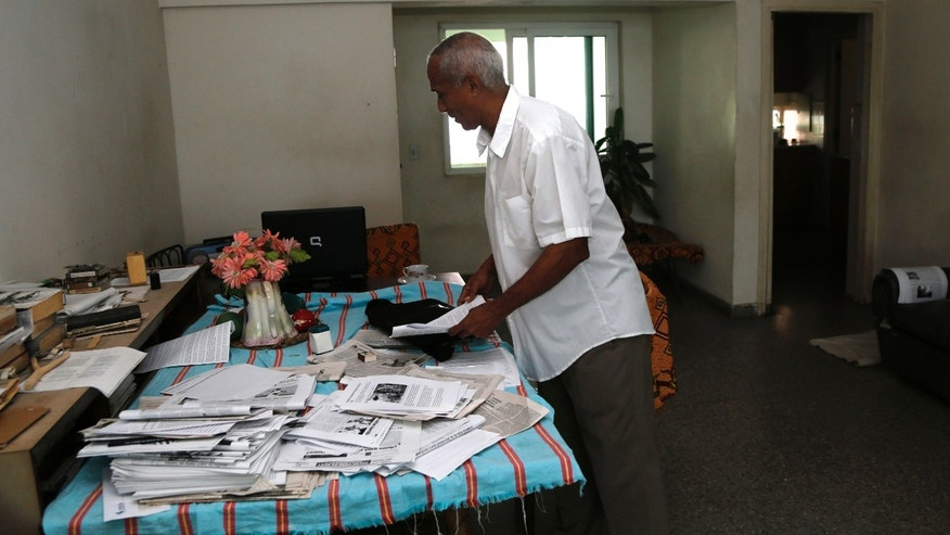 In this April 16, 2015 photo, former government lawyer turned dissident Hildebrando Chaviano, who is taking a course in independent journalism led by U.S. professors via video link inside the U.S. Interests Section, arranges papers in the living room of his home in Havana, Cuba. The journalism program, which is taught for free along with English and information technology, has come under renewed criticism in Cuba amid talks to restore full diplomatic relations between the islandâs Communist government and the United States for the first time in more than 50 years. (AP Photo/Desmond Boylan)