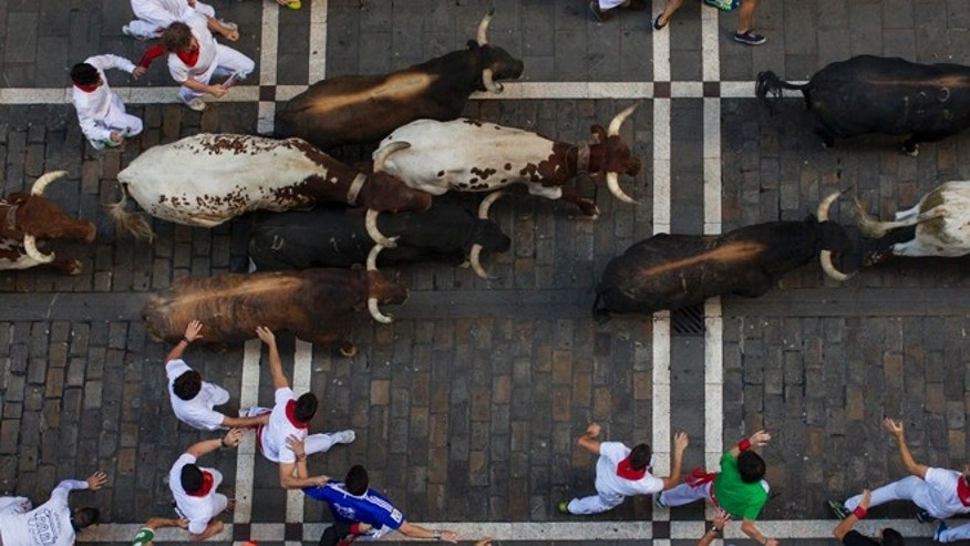 Victoriano del Rio fighting bulls run after revelers during the running of the bulls at the San Fermin festival in Pamplona, Spain, Thursday, July 9, 2015. Revelers from around the world arrive in Pamplona every year to take part in some of the eight days of the running of the bulls. (AP Photo/Andres Kudacki)