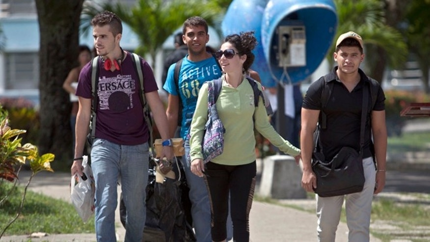 In this July 11, 2014 file photo, Cuban students exit Marta Abreu Central University in Santa Clara, Cuba. Since the U.S. eased travel restrictions in 2015, several colleges have struck agreements with Cuban schools to create exchange programs for students and faculty. More American colleges are planning study trips to Cuba. Both sides are exploring research collaborations. (AP Photo/Franklin Reyes, File)