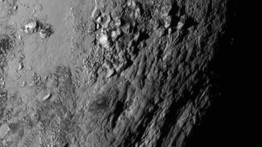 Tuesday, July 14, 2015 Image provided by NASA on Wednesday shows a region near Pluto's equator with a range of mountains captured by the New Horizons spacecraft.