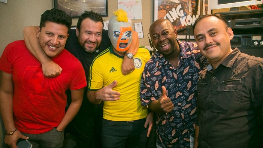 "In this Thursday, July 23, 2015 photo, Radio DJs, Daniel Perez, ""El Garbanzo, far left,"" and Oswaldo Diaz, ""Erazno,"" third from left, pose with show producers: Raul Martinez, ""El Diablito,"" Edwin Roman and Hessler De la Cruz, far right. El Show de Erazno y La Chokolata"" radio show in Los Angeles. The program offers to help immigrants wondering if girlfriends and boyfriends, wives and husbands left behind or deported back to Mexico and Central America are being faithful. They call in, reveal their woes and then listen offline as the host calls their unsuspecting partner and offers the chance to send a free heart-shaped box of chocolate to their romantic interest. Diaz's show is broadcast by Entravision and reaches over 2 million people nationwide. (AP Photo/Damian Dovarganes)"