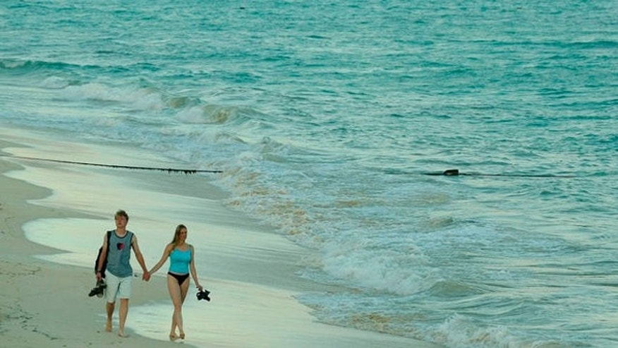 A couple of tourists walk on the beach at sunset in Playa del Carmen, south of Cancún, Mexico. (AP Photo/Guillermo Arias)