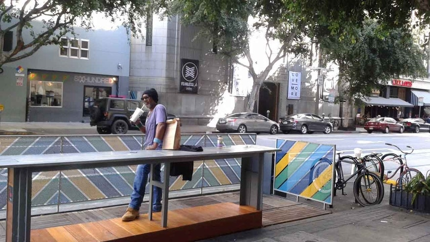 A pedestrian stands by a parklet in downtown L.A., California.