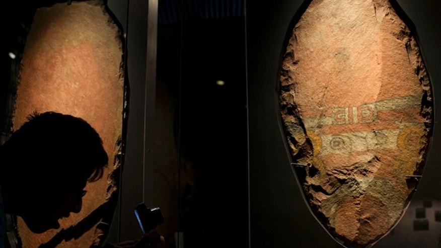 A man bends down to take a picture of a giant, symbolic sacrificial knife, part of a display of items offered to the Aztec god Xochipilli, at the Templo Mayor museum in Mexico City, Friday, Aug. 7, 2015. The Aztecs usually sacrificed quails to Xochipilli, rather than still-beating human hearts. And he was worshipped at vast poetry and music festivals, rather than martial displays. (AP Photo/Rebecca Blackwell)