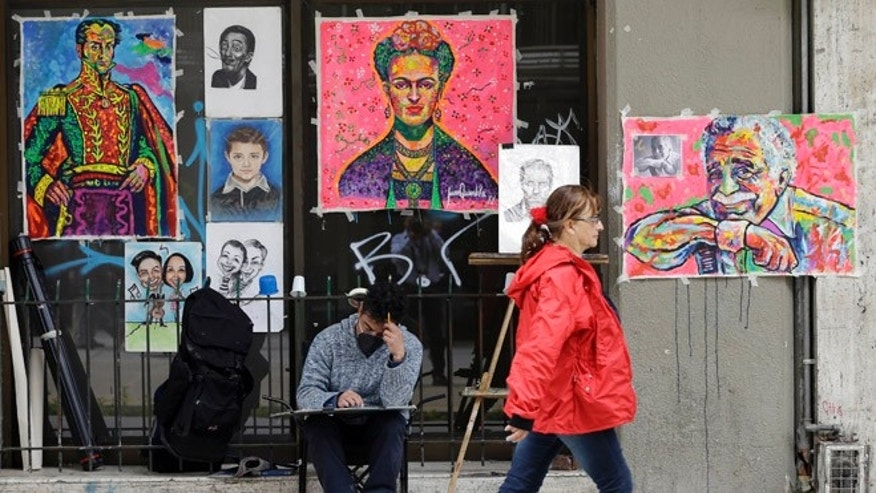 An artist sits in front of his paintings for sale, including one of Colombia's late novelist Gabriel Garcia Marquez, right, in downtown Bogota, Colombia, Tuesday, Aug. 11, 2015, along with paintings of Mexican artist Frida Kahlo, center, and independence hero Simon Bolivar. The cremated remains of Nobel Prize-winning novelist Gabriel Garcia Marquez are making their return journey home to Colombia and starting in December will be exhibited in the Caribbean city of Cartagena where he began his writing career. (AP Photo/Fernando Vergara)
