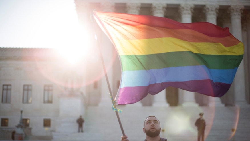 WASHINGTON, DC - APRIL 28: Same-sex marriage supporter Vin Testa, of Washington, DC, waves a rainbow pride flag near the Supreme Court, April 28, 2015 in Washington, DC. On Tuesday the Supreme Court will hear arguments concerning whether same-sex marriage is a constitutional right, with decisions expected in June. (Drew Angerer/Getty Images)