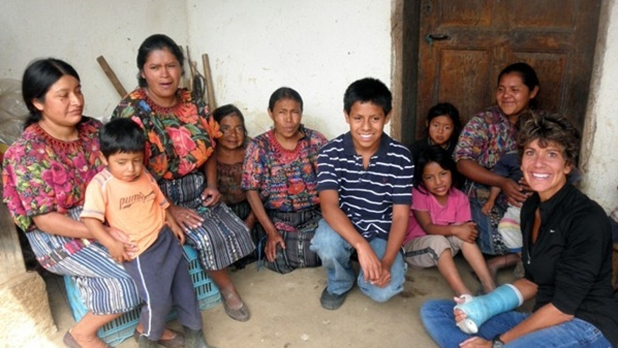 ADVANCE FOR USE SUNDAY, SEPT. 6, 2015 AND THEREAFTER - In this July 2012 photo provided by the family, Jake Niergarth, 14, center with striped shirt, and his adoptive mother, Lisa, right, pose for a photo with residents of a rural area outside of Chichicastenango, Guatemala. When the Niergarths adopted Jake through a major U.S. adoption agency in 1999, they learned his birth mother's name, but little else about her or why she relinquished Jake. (Steve Niergarth via AP)
