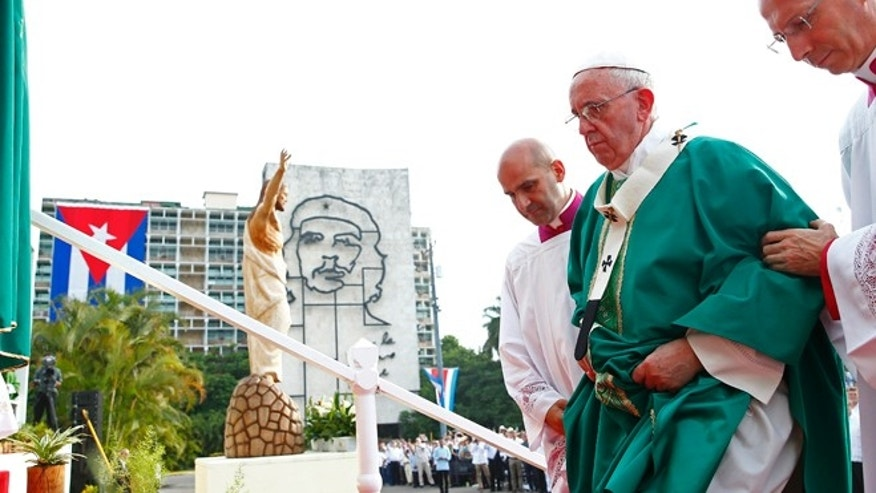"Pope Francis is helped to the altar as he arrives to celebrate Mass in Revolution Square in Havana, Cuba, Sunday, Sept. 20, 2015, where a sculpture of revolutionary hero Ernesto ""Che"" Guevara decorates a nearby government building. Pope Francis opens his first full day in Cuba on Sunday with what normally would be the culminating highlight of a papal visit: Mass before hundreds of thousands of people in Havana's Revolution Plaza.  (Tony Gentile/POOL via AP)"