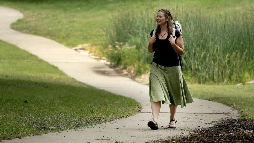 In this photo taken Aug. 28, 2015, Bethany Hughes walks through a park in Kansas City, Mo. as she prepares for her upcoming hike through the Americas. Hughes hopes to become the first woman to trek from the southern tip of South America to the northern tip of Alaska all by non-motorized means. (AP Photo/Charlie Riedel)