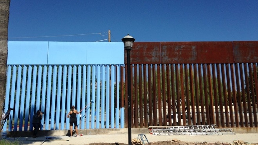Artist Ana Teresa Fernandez paints the Sonora border fence in Nogales, Mexico,Tuesday, Oct. 13, 2015.