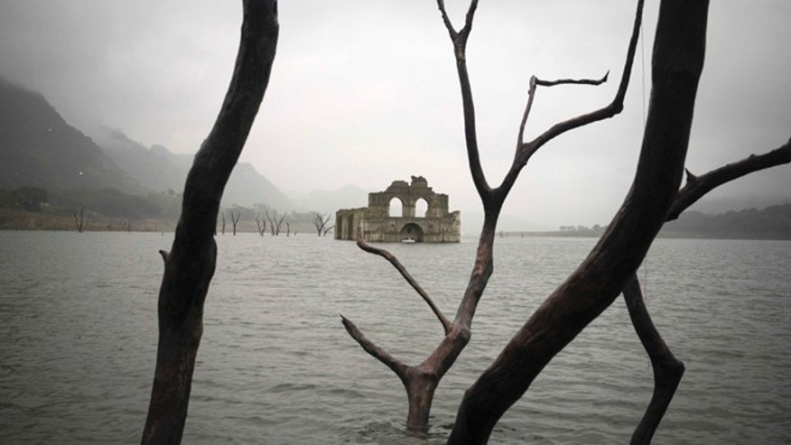 The remains of a mid-16th century church known as the Temple of Santiago, as well as the Temple of Quechula, is visible from the surface of the Grijalva River, which feeds the Nezahualcoyotl reservoir, due to the lack of rain near the town of Nueva Quechula, in Chiapas state, Mexico, Friday, Oct. 16, 2015. The temple, built by Dominican friars in the region inhabited by the Zoque people, was submerged in 1966 when the Nezahualcoyotl dam was built. (AP Photo/David von Blohn)
