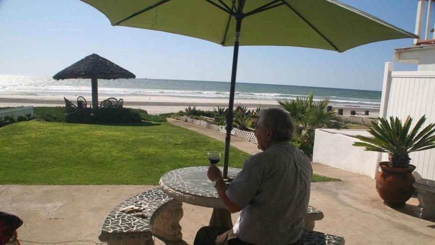 Herb Kinsey savoring a glass of wine by the shore.