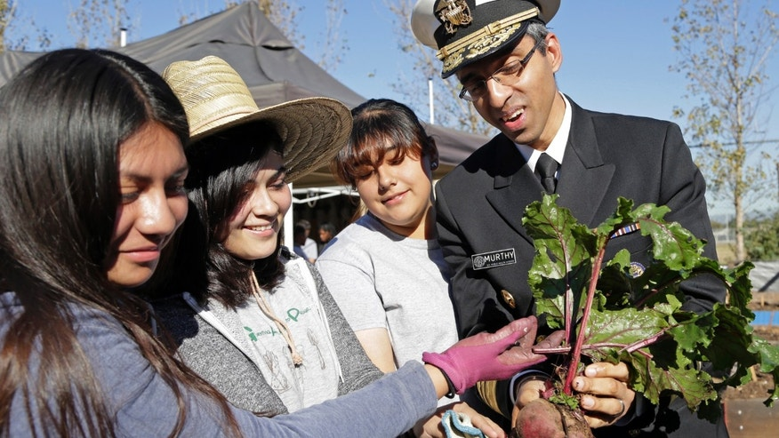 U.S. Surgeon General Vivek Murthy and John C. Fremont High School students hold a beet grown in the school's Gardening Apprenticeship Program plot on the campus south of downtown Los Angeles Friday, Nov. 20, 2015. Murthy visited the partnership between community organizations and the high school to support healthy initiatives in neighborhoods starved for fresh produce and grappling with childhood obesity. Students involved in the 12-week after-school gardening apprenticeship program learn to grow food and cook healthy dishes, pulling from kumquat and lime trees and planters filled with potatoes, peas and beets.(AP Photo/Nick Ut)