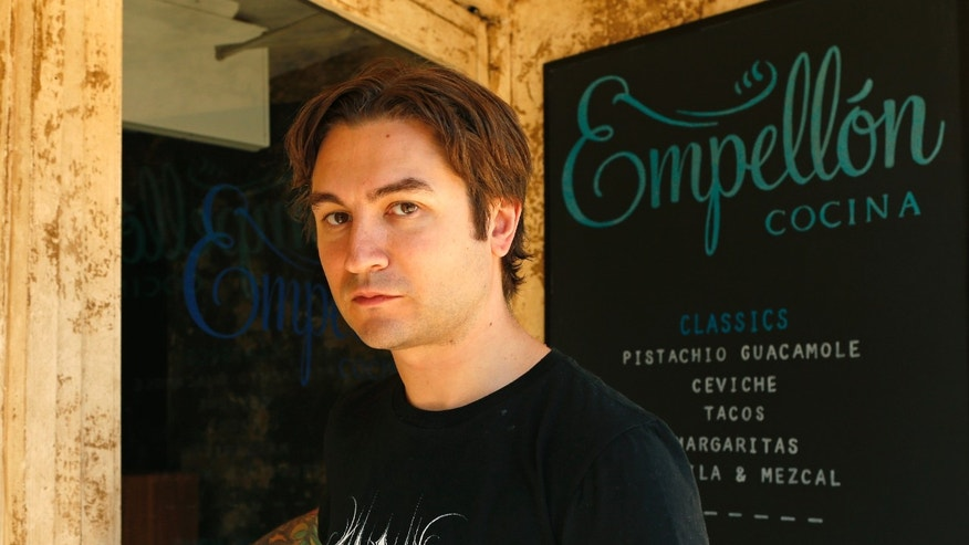 In this Oct. 20, 2015 photo, acclaimed pastry chef Alex Stupak, who shifted over to Mexican food several years ago, poses for a photograph in front of his Mexican restaurant Empellon Cocina, in the East Village neighborhood in New York. Stupak, who worked in kitchens known for molecular gastronomy, has come out with a cookbook that approaches tacos in a whole different way. (AP Photo/Kathy Willens)