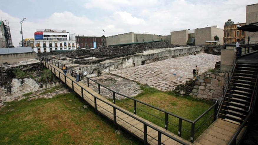 In this Oct. 3, 2006 photo, people visit the archaeological site, the Templo Mayor, in Mexico City. A Mexican archaeologist said Monday, Nov. 30, 2015, his team has discovered, at the archaeological site, a long tunnel leading into the center of a circular platform where Aztec rulers were believed to be cremated. The Aztecs are believed to have cremated the remains of their leaders during their 1325-1521 rule, but the final resting place of the cremains has never been found. (AP Photo/ Claudio Cruz, File)