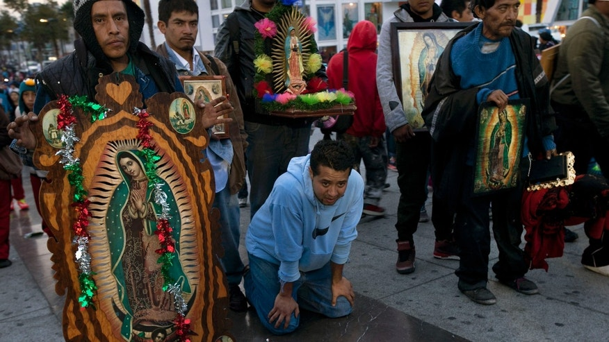 A pilgrim pauses as he crosses on his knees, the main doors of the Basilica of Guadalupe as others carry images of the Virgin of Guadalupe in Mexico City, Saturday Dec. 12, 2015. Pilgrims gathered at the basilica for the feast day of the Virgin of Guadalupe, Mexico's most popular religious and cultural image. (AP Photo/Marco Ugarte)
