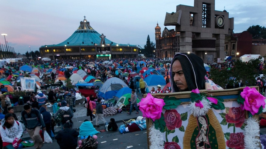 A man carries an image of the Virgin of Guadalupe as other pilgrims begin to wake up as they wait for mass after spending the night in the main patio of the Basilica of Guadalupe in Mexico City, Saturday Dec. 12, 2015. Hundreds of thousands of people from all over the country converge on Mexico's holy Roman Catholic site, many bringing with them images or statues of Mexico's patron saint to be blessed, marking the Virgin's Dec. 12 feast day.  (AP Photo/Marco Ugarte)