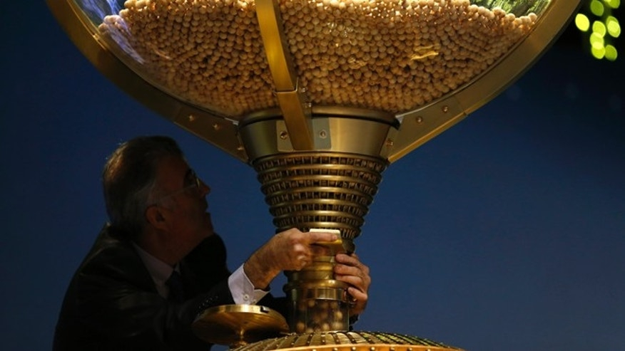 "A worker opens a trap-door in a giant drum to let the balls bearing ticket numbers fall into a lower compartment before the start of Spain's Christmas lottery, in Madrid, Tuesday, Dec. 22, 2015. Celebrations were guaranteed Tuesday in the southern beach town of Roquetas de Mar, southern east Spain, where tickets bearing the top prize number of 79140 in Spain's Christmas lottery, known as ""El Gordo"" (The Fat One) were sold. The number appeared on 1,600 tickets, known as decimos (tenths) with each holder winning 400,000 euros ($434,800). The tickets are usually sold in many different lottery sales points making it virtually impossible to win the entire 640 million euros assigned to the top prize number. (AP Photo/Francisco Seco)"