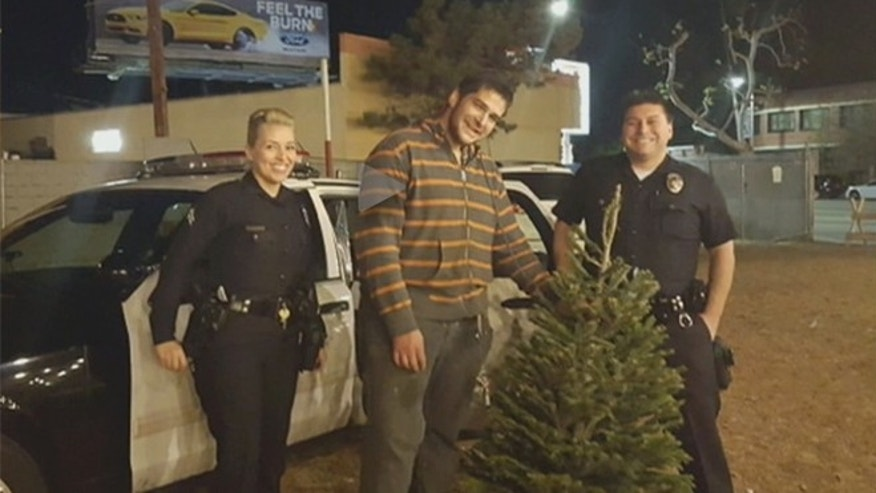 Officers Natalie Nuñez (left) and Abel Torres (right) with the donor of Herman Perry's Christmas tree. (Image: Fox 11 Los Angeles)