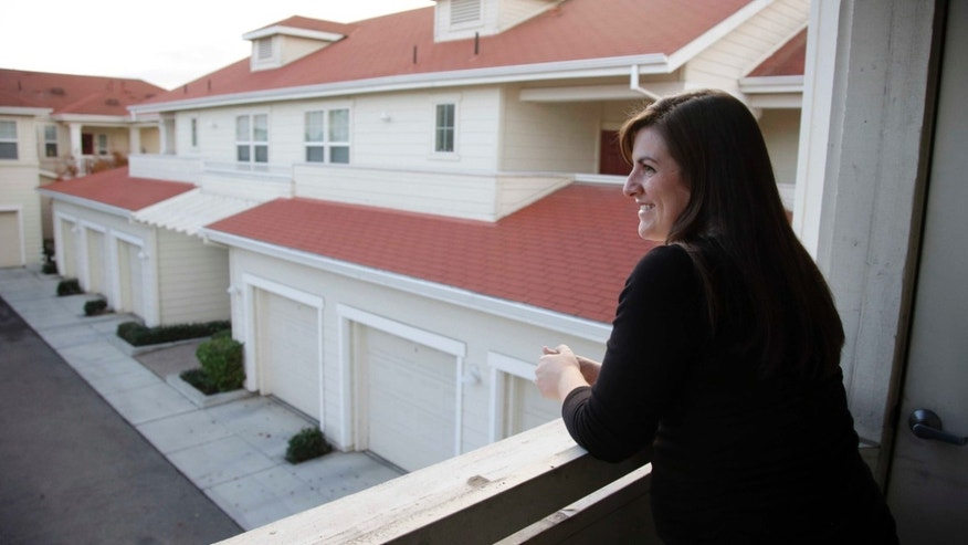 In this Dec. 11, 2015, photo, Katy Howser, a kindergarten teacher in the Santa Clara School District, looks out from the balcony of her apartment at Casa Del Maestro, an apartment complex for teachers, in Santa Clara, Calif. School districts in high cost-of-living areas and rural communities that have long struggled to staff classrooms are considering buying or building rent-subsidized apartments as a way to attract and retain teachers amid concerns of a looming shortage. (AP Photo/Marcio Jose Sanchez)