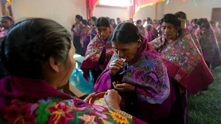 In this Jan. 16, 2016 photo, a Tzotzil Indian lay woman distributes Holy Communion during a Catholic Mass in honor of the Christ of Esquipulas in Chajtoj, Chiapas state, Mexico. Pope Francis travels to Mexico Feb. 12-18, that includes a one-day visit to Chiapas, where he will celebrate Mass and lunch with indigenous people. (AP Photo/Eduardo Verdugo)