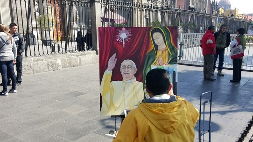 Jorge Santamaria paints Pope Francis and the Virgin of Guadalupe in front of Mexico City's main cathedral. (Jan-Albert Hootsen/Fox News Latino)