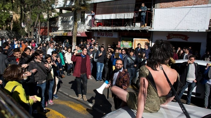 In this March 10, 2016 photo, students watch Arturo Hernandez sit on a car wearing a dress and Alex Marin y Kall carrying a megaphone as the pair pretend to be a model and car salesman selling the double-parked car, as a humorous tactic to get the driver to move from a clogged street outside the Autonomous Technological Institute of Mexico in Mexico City. The pair are comedians who head a band of volunteer YouTube celebrities known as the âSuper Civicos.â In a city as violent and chaotic as Mexico City, the strategy often ends in confrontation, as Hernandez has been beaten several times. (AP Photo/Rebecca Blackwell)