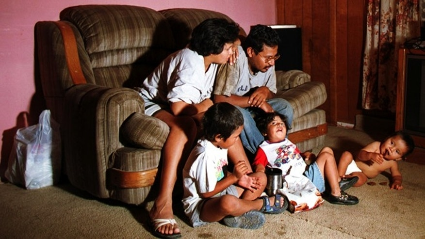 Lorenzo Alvarez, his wife Angelica Alvarez and their three children watch TV at their home in a colonia on the outskirts of El Paso, Texas. (Photo by Joe Raedle/Newsmakers)