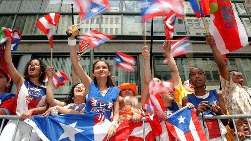 NEW YORK - JUNE 13:  Spectators watch the ninth annual Puerto Rican Day Parade pass by June 13, 2004 in New York City. Tens of thousands of people lined Fifth Avenue for the parade.  (Photo by Stephen Chernin/Getty Images)