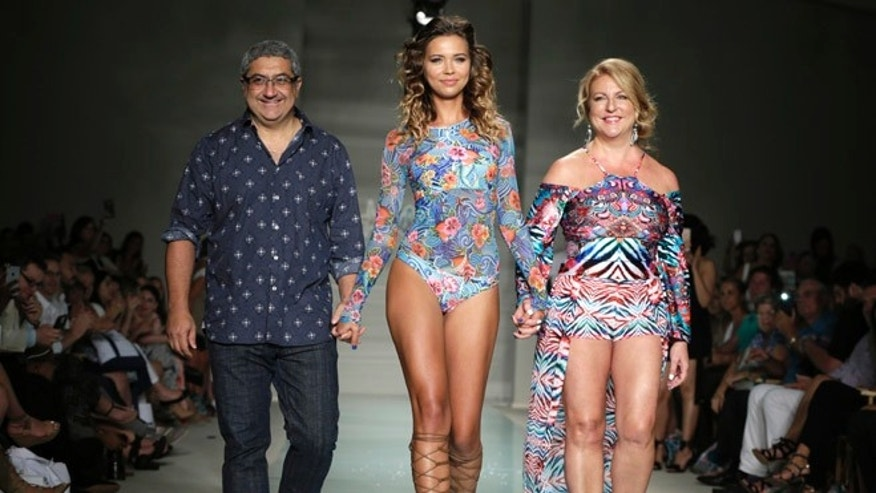 "A model walks down the runway with designers Augusto Hanimian, left, and Lourdes ""Luli"" Hanimian during the Luli Fama swimwear show, Saturday, July 16, 2016, in Miami Beach, Fla. (AP Photo/Lynne Sladky)"