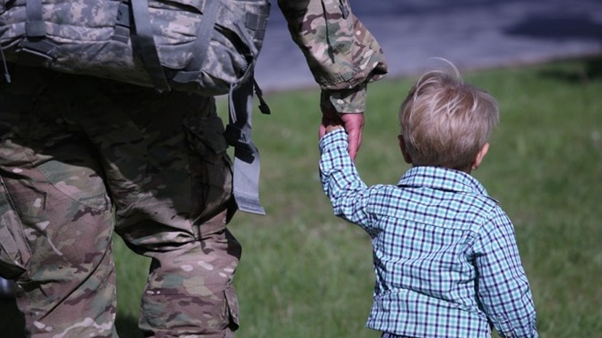 A father and son walk from a welcome-home ceremony for soldiers returning from Iraq on May 17, 2016 at Fort Drum, New York.  (Photo by John Moore/Getty Images)