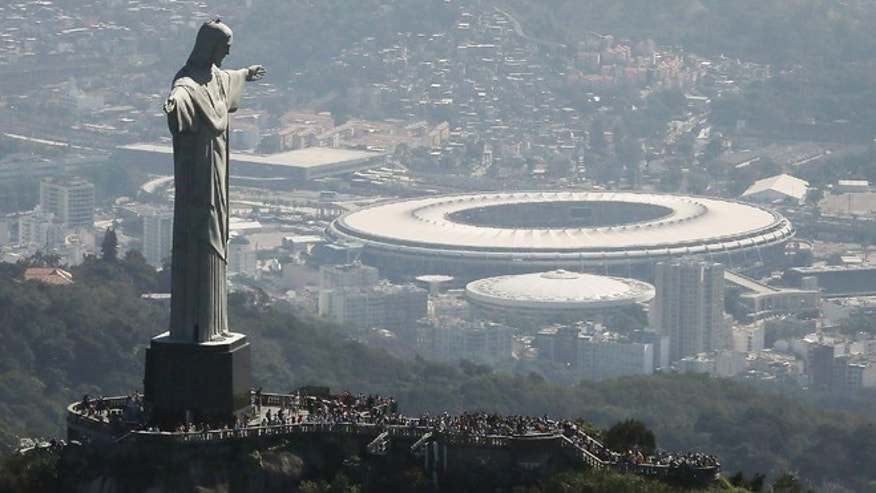RIO DE JANEIRO, BRAZIL - JULY 04:  Visitors gather beneath the Christ the Redeemer statue as Maracana stadium, site of the Olympic opening ceremonies, stands in the background on July 4, 2016 in Rio de Janeiro, Brazil. July 5 marks the one-month mark to the beginning of the Rio 2016 Olympic Games with an economic crisis, political turmoil and Zika virus fears roiling the country.  (Photo by Mario Tama/Getty Images)