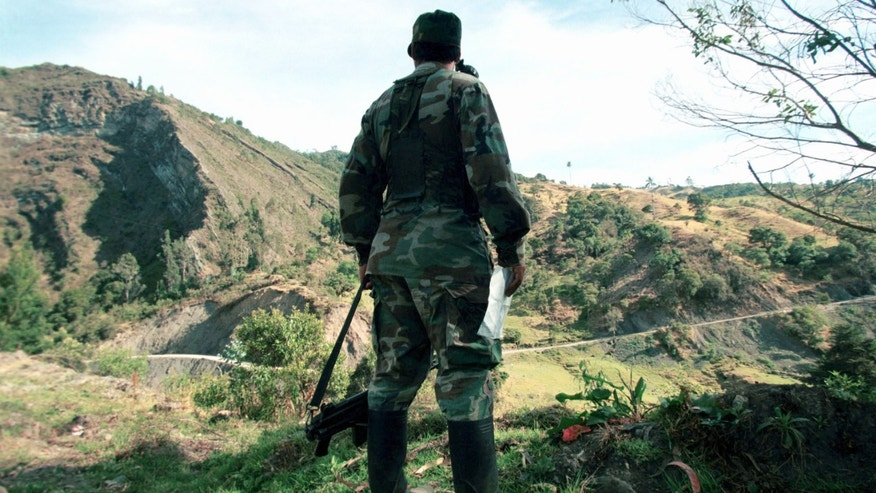 "402036 04: (COLOMBIA OUT) Guerrilla commander Oscar Rondon of the Revolutionary Armed Forces of Colombia (FARC) stands March 7, 2002 in the mountains near Bogota, Sumapaz, Colombia. The group has ""invited peacefully"" the Colombian people to boycott Senatorial elections on March 10, as the FARC has branded them antidemocratic. (Photo by Carlos Villalon/Getty Images)"