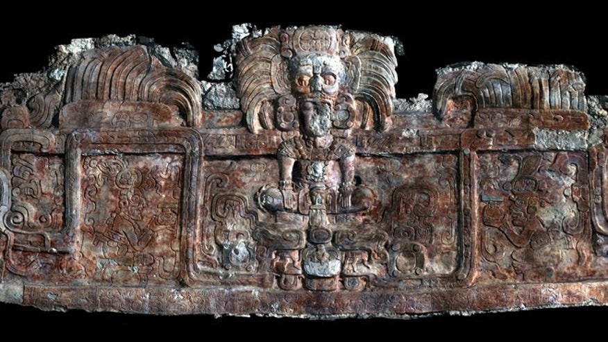 A frieze discovered at Holmul. The main figure is a king wearing an avian sun god headdress emerging from a sacred mountain spirit head amid feathered serpents. His name, Tzahb Chan Yopaat appears twice, in a medallion on his headdress and in the inscription below the figure. (Photo: A. Tokvinine, U. Alabama)