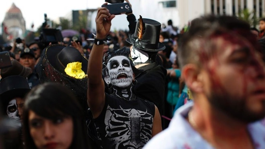 A man in costume takes a selfie during a Day of the Dead parade along Mexico City's main Reforma Avenue, Saturday, Oct. 29, 2016. Hollywood movies, zombie shows, Halloween and even politics are fast changing Mexico's Day of the Dead celebrations, which traditionally consisted of quiet family gatherings at the graves of their departed loved ones bringing them music, drink and conversation. (AP Photo/Dario Lopez-Mills)