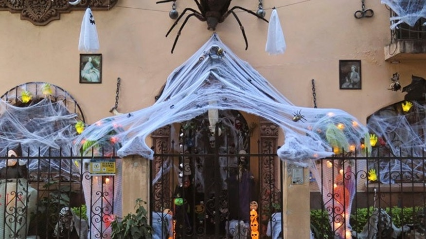 "A large, fake spider and its web cover the entrance of Samuel Soriano's home ahead of Halloween in Mexico City, Friday, Oct. 28, 2016. Soriano and his wife also have a traditional Day of the Dead shrine in their dining room, with portraits of departed loved ones, candles, decorative skulls and marigold flowers. ""We also celebrate Day of the Dead...there's no reason to see it as a contradiction,"" said Soriano. (AP Photo/Peter Orsi)"