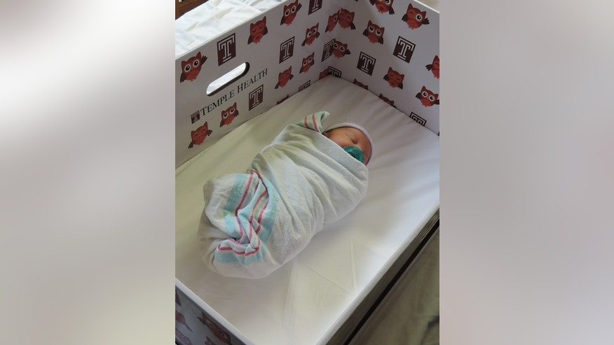 A newborn in a Temple University Hospital baby box, which serves as a bassinet.